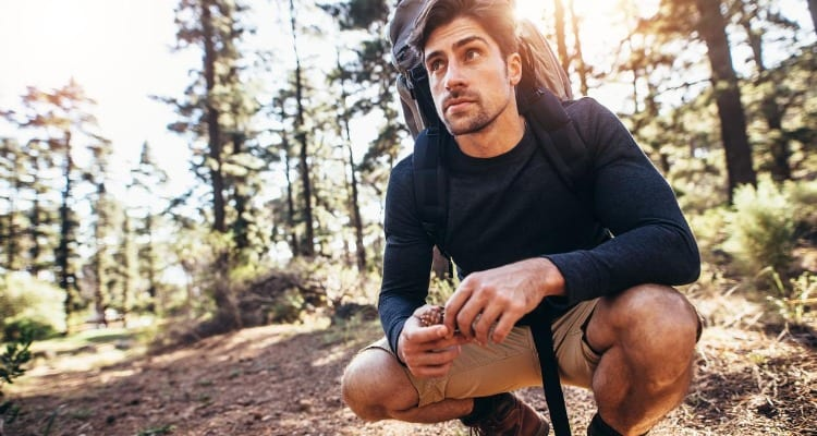 Man hiking and meditating to relax