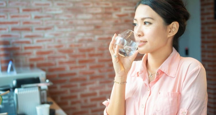Woman drinking water at work in order to stay adequately hydrated