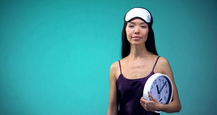 Woman holding a clock to focus on her sleep routine