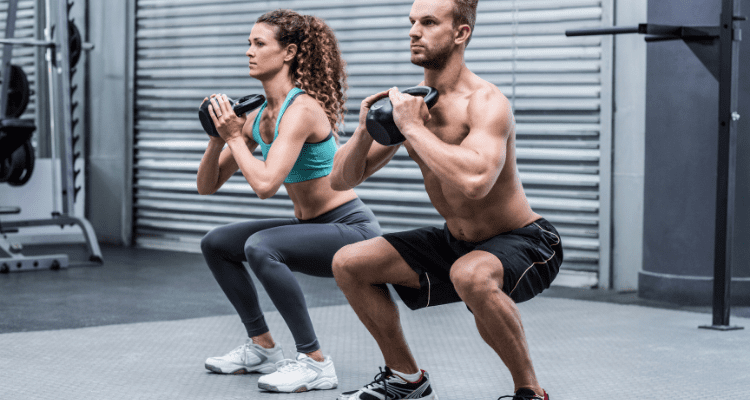 Man and woman doing kettlebell front squats together