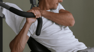 Man using a seated military press shoulder exercise machine, experiences a shoulder injury and will likely need shoulder rehab exercises.