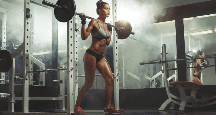 Woman doing free weight barbell squats to build muscle and strength