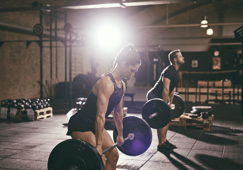 man and woman doing clean and press workout to build muscle