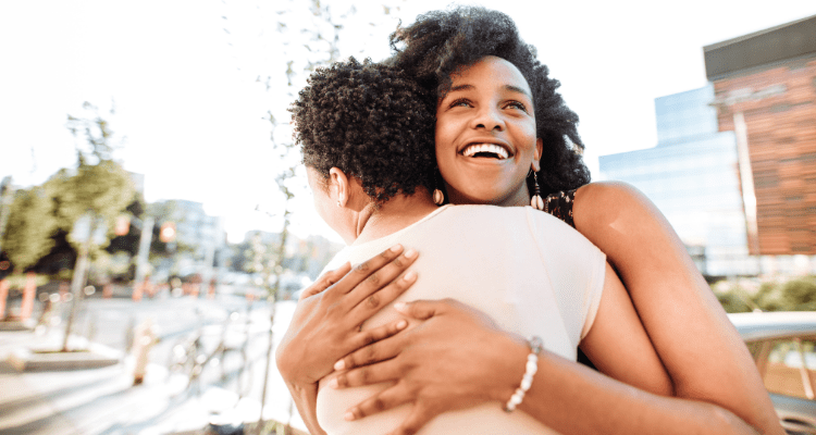 Woman being hugged in a joyous moment after donating her plasma