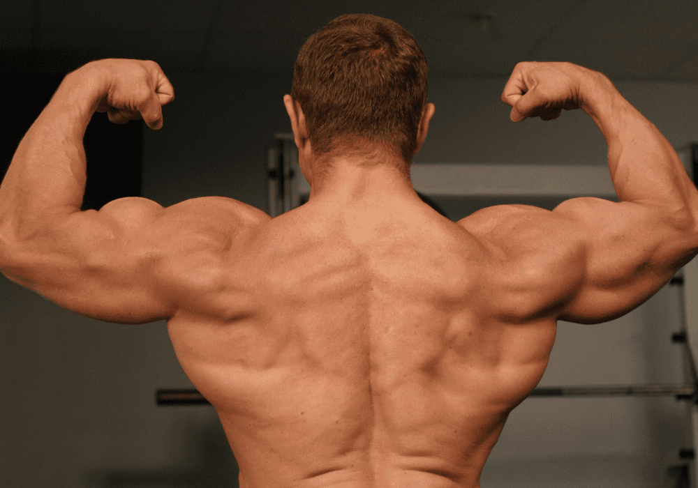 Man flexing after performing a series of supersets at the gym with David Aston