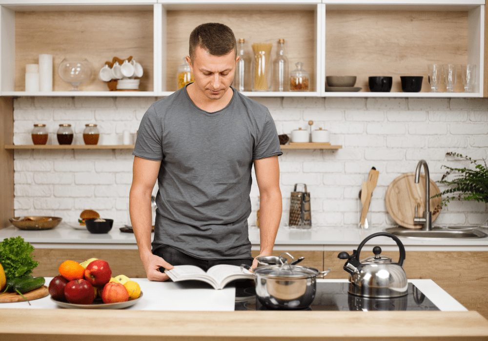 Man using the Superhuman Cookbook to prepare some easy and delicious muscle growth recipes.