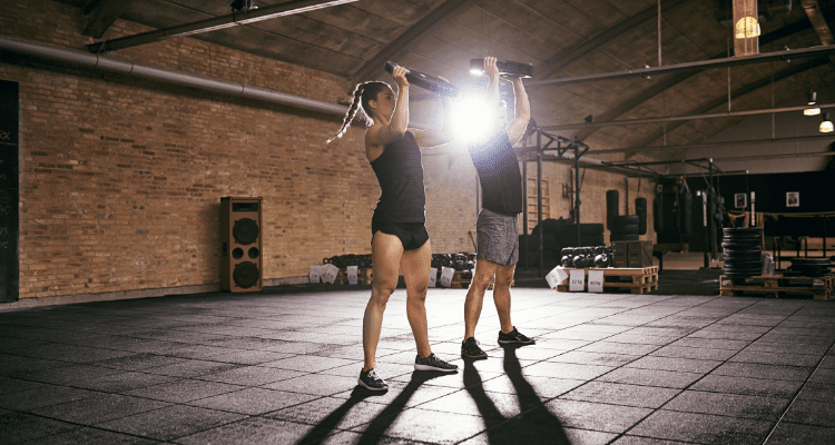Man and woman performing a pre exhaustion superset at the gym
