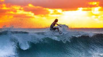Local Showing us how to surf a wave during sunset.jpeg