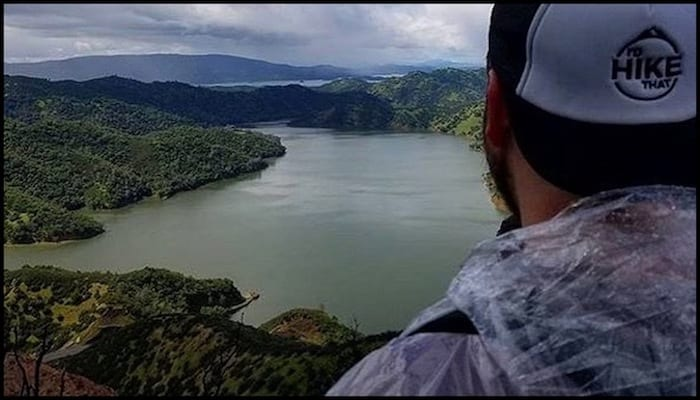 David Aston Wearing a Poncho During a Rainy Hike Overlooking a Body of Water | AdventureHacks