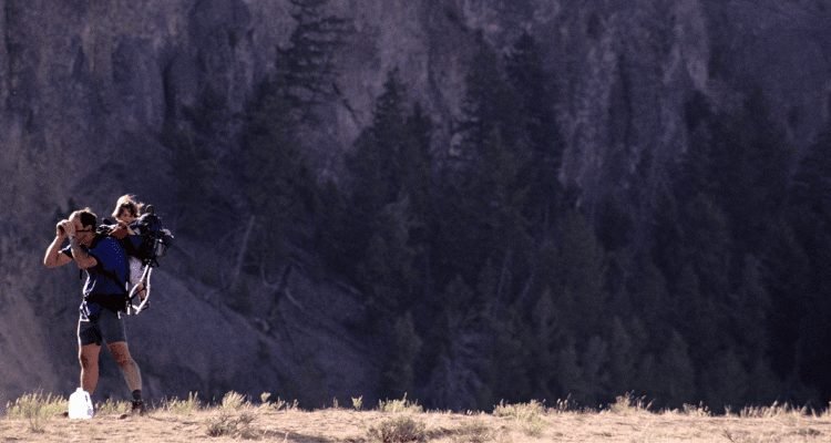 AdventureHacks nomad and his child peaking through binoculars at a herd of Bison in Southwest Yellowstone
