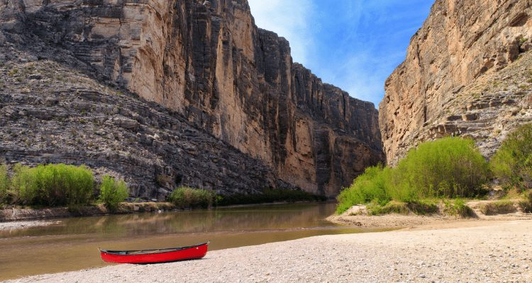 David Aston takes a photo break of his canoe on a beach within the Grand Canyon