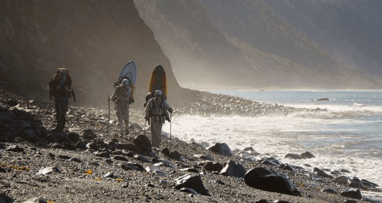 David Aston and friends hiking the lost coast with their surf boards looking for the perfect spot