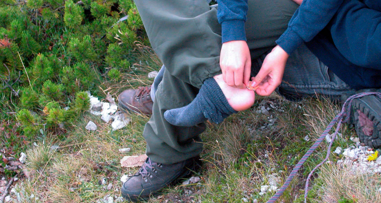 Man treating a blister during a hiking trip