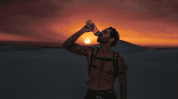 hiker drinking water during an evening hike in the desert