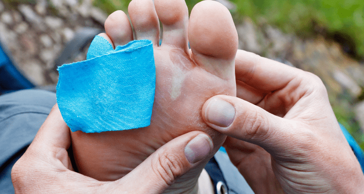 Hiker using tape as padding on her feet to prevent blisters