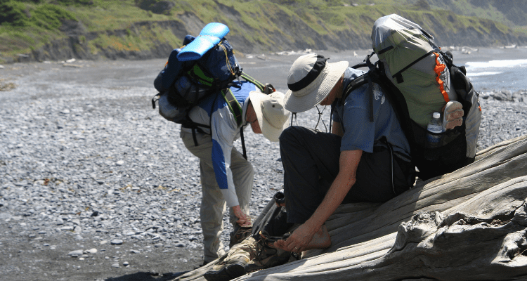 Hikers inspecting their feet during a long hike on The Lost Coast