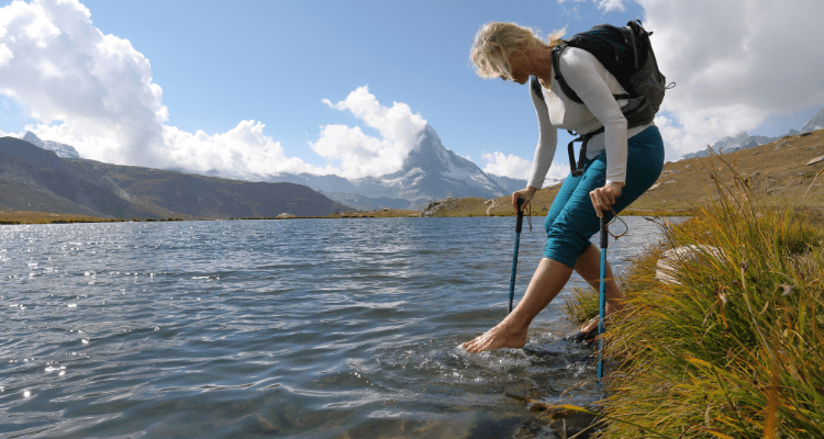 Woman removing her hiking shoes to cross water