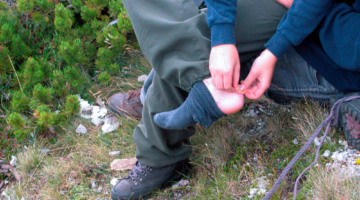 hiker treating his blisters while on the trail