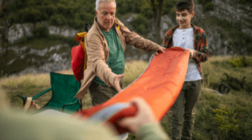 Father teaching his son how to care for a sleeping bag after using it during a camping trip